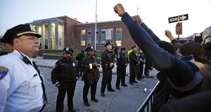 Marchers raise their fists in front of Baltimore police guarding the department's Western District police station on Wednesday during a march for Freddie Gray in Baltimore. Gray died from spinal injuries about a week after he was arrested and transported in a police van. (AP Photo/Alex Brandon)
