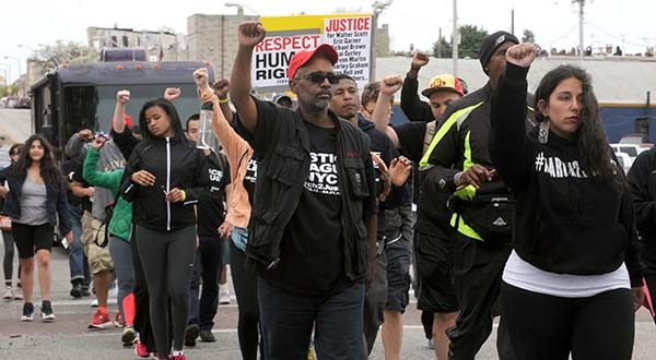 Citizens and groups such as the Justice League of NYC protest on Sunday in Baltimore following the death of Freddie Gray. Gray, 25, of Baltimore, died Sunday at a hospital, a week after he was hurt following an arrest. (Algerina Perna/The Baltimore Sun via AP)