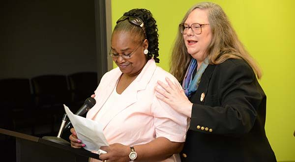 Kelly Damon, and Ellen Callegary, Esq., President of the Board of Directors for Mosaic Community Services, stand together after Kelly talked about her care at Mosaic. (The Daily Record / Maximilian Franz)