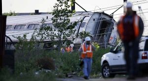 Emergency personnel walk near the scene of a deadly train wreck on Wednesday in Philadelphia. An Amtrak train headed to New York City derailed and crashed in Philadelphia on Tuesday night. (AP Photo/Mel Evans)