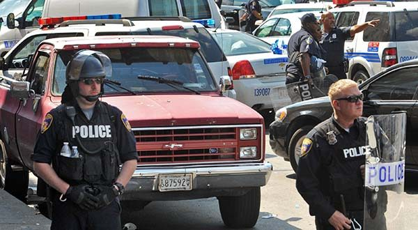 Police stand behind tape Monday in Baltimore. (Amy Davis/The Baltimore Sun via AP)