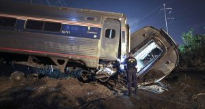 Emergency personnel work the scene of a deadly train wreck in Philadelphia May 12. Five years ago, federal safety officials proposed requiring video cameras in train cabs, but it didn't happen. Amtrak said Tuesday it will install video cameras inside locomotive cabs to record the actions of train engineers.  (AP Photo/ Joseph Kaczmarek, File)