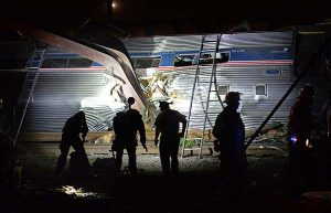 Police and Fire Rescue personnel work the scene of a deadly train wreck on Tuesday in Philadelphia. An Amtrak train headed to New York City derailed and tipped over in Philadelphia on Tuesday night, mangling the front of it, tearing the cars apart and killing several people. (Tom Gralish/The Philadelphia Inquirer via AP)