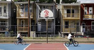 In this May 9 picture, boys ride bicycles past a basketball backboard displaying an inspirational message at a park in the Reservoir Hill neighborhood of Baltimore. From 2011 to 2013, Census figures show an additional 77 families with incomes above $200,000 settled in Baltimore's 21217 ZIP code, which includes Reservoir Hill and the Sandtown-Winchester neighborhood where Freddie Gray lived. (AP Photo/Patrick Semansky)
