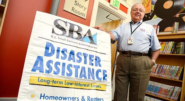 Edward Williams, Field Operations Specialist with the SBA, U.S. Small Business  Administration, stands by a Disaster Assistant long-term Low interest Loans sign that is posted outside of their temporary office at the Enoch Pratt Free Library at the Penn-North intersection in North West Baltimore.  (The Daily Record/Maximilian Franz).