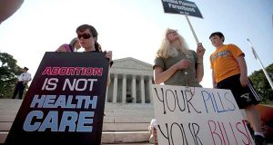 In this June 28, 2012, file photo, demonstrators pray outside the Supreme Court in Washington before a landmark decision on health care. Many Americans doubt that the Supreme Court can rule fairly in the latest litigation jeopardizing President Barack Obama's health care law. The Associated Press-GfK poll finds only 1 in 10 are highly confident that the justices will rely on objective interpretations of the law instead of their personal opinions. Nearly half (48 percent) are not confident of the court's impartiality. (AP Photo/Evan Vucci, File)