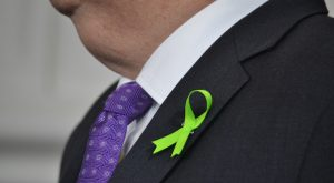 Gov. Larry Hogan wears a green ribbon symbolizing support for people diagnosed with blood cancers. (Bryan P. Sears/The Daily Record)