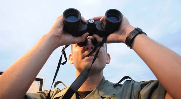 Maryland Department of Natural Resources Police Officer Steven Hunter looks through some binoculars in 2012, just south of Annapolis. (Maximilian Franz/The Daily Record).