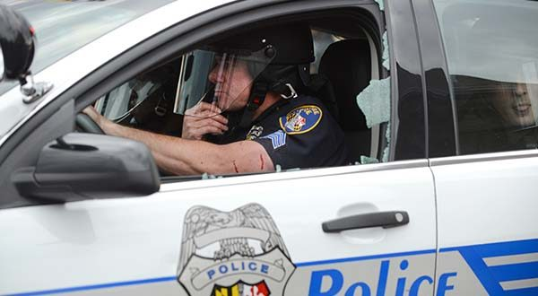 A police officer driving a squad car with a shattered window has blood on his arm on April 27 during the riots on North avenue. (The Daily Record / Maximilian Franz)