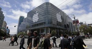 In this June 2, 2014 file photo, pedestrians cross the street in front of the Moscone Center, which is hosting the Apple Worldwide Developers Conference, in San Francisco. Apple is expected to announce its new paid streaming-music service at its annual conference for software developers, which kicks off Monday, June 8, 2015. (AP Photo/Jeff Chiu, File)