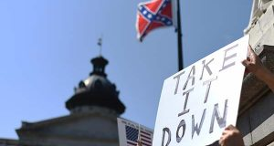 Protesters hold a sign during a rally to take down the Confederate flag at the South Carolina Statehouse, Tuesday in Columbia, S.C. (AP Photo/Rainier Ehrhardt)