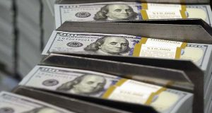In this Sept. 24, 2013, file photo, freshly-cut stacks of $100 bills make their way down the line at the Bureau of Engraving and Printing Western Currency Facility in Fort Worth, Texas.(AP Photo/LM Otero, File)