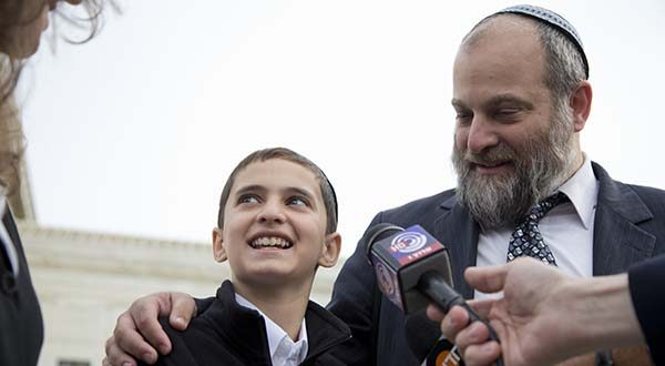 In this Nov. 3, 2014 file photo, Menachem Zivotofsky and his father Ari Zivotofsky speaks to media outside the Supreme Court in Washington. The Supreme Court has struck down a disputed law that would have allowed Americans born in Jerusalem to list their birthplace as Israel on their U.S. passports. It's an important ruling that underscores the president's authority in foreign affairs. The court ruled 6-3 Monday that Congress overstepped its bounds when it approved the law in 2002. It would have forced the State Department to alter its long-standing policy of not listing Israel as the birthplace for Jerusalem-born Americans. (AP Photo/Carolyn Kaster, File)