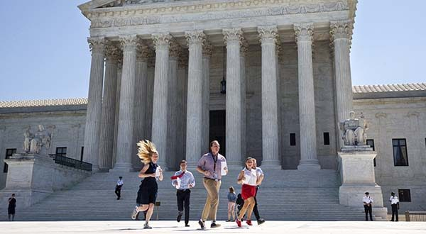 New interns run with a decision across the plaza of the Supreme Court in Washington in June 2015. (AP Photo/Jacquelyn Martin)