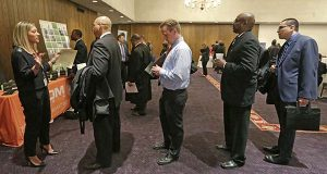 In this April 22, 2015 photo, Bianca Medici, left, a corporate recruiter for CDM Media, speaks with job applicants during a National Career Fairs job fair in Chicago. The Labor Department releases weekly jobless claims on Thursday, May 14, 2015. (AP Photo/M. Spencer Green)