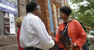In this photo taken Tuesday, Baltimore Mayor Stephanie Rawlings-Blake, right, speaks with a resident outside of vacant homes after a ceremony to kick off their restoration in Baltimore. For many in Baltimore, the memory of April's riots - and the mayor's handling of the unrest - is still fresh. After firing embattled police commissioner Anthony Batts, who bore the brunt of public outrage, Rawlings-Blake remains the primary figure head of a city that is still reeling from the damage it suffered. (AP Photo/Patrick Semansky)