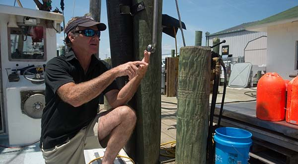 """In this July 17 photo, Capt. Kerry Harrington discusses the installation of cameras on his fishing boat, which the National Oceanic and Atmospheric Administration has required since June, at the commercial harbor in West Ocean City. The technology allows the administration to verify what pelagic longline fishermen are reporting when it comes to things such as discarding dead fish. But to Harrington, it feels like Big Brother is watching. """"You can imagine the intrusiveness of it,"""" he said. """"Under the microscope all day long."""" (Rachael Pacella/The Daily Times via AP)"""