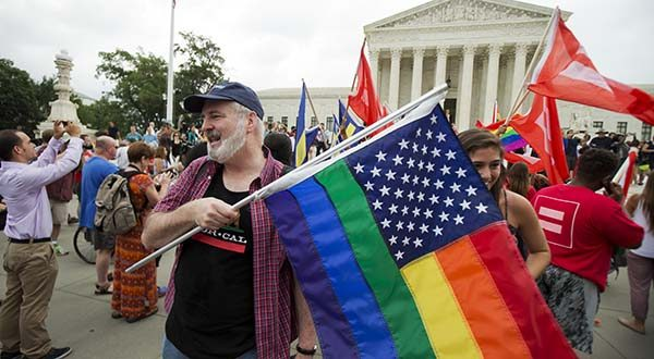 In this June 26, 2015 photo, supporters celebrate outside the U.S. Supreme Court in Washington after the court declared that same-sex couples have a right to marry anywhere in the United States.  Attorney General Loretta Lynch says the government will make federal marriage benefits available to same-sex couples following a Supreme Court decision last month that legalized same-sex marriage.   (AP Photo/Manuel Balce Ceneta)