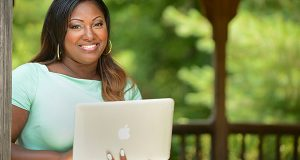 Nakia Gray, Esq., Attorney at Law, poses for a photo with her laptop under a gazebo in a park. (The Daily Record / Maximilian Franz)