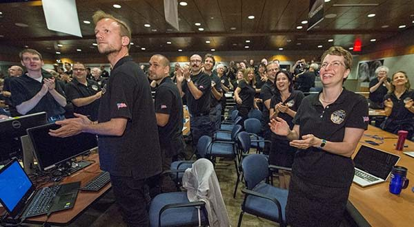 Members of the New Horizons science team react to seeing the spacecraft's last and sharpest image of Pluto before closest approach later in the day, Tuesday at the Johns Hopkins University Applied Physics Laboratory (APL) in Laurel. NASA's New Horizons spacecraft was on track to zoom within 7,800 miles (12,500 kilometers) of Pluto on Tuesday. (Bill Ingalls/NASA via AP)