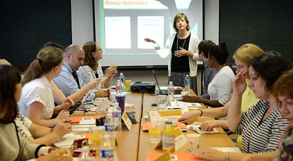 Sue Rogan, director of financial education at the Maryland CASH Campaign, plays the Money Habitudes card game with a delegation from Belarus that visited the Maryland CASH campaign Thursday to learn about financial literacy in the United States. (Maximilian Franz/The Daily Record)
