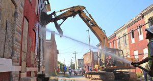 Julius Henson, of the Berea-Eastside Community Association, takes the first whack at ripping down a vacant home in the 1500 block of North Rose Street on Tuesday.  (The Daily Record / Adam Bednar)