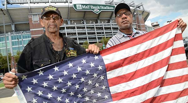 Founders of the United Veterans Coalition Baltimore Chapter, Vietnam Veteran Robert Valentine, left,  and Ret SSGT Robert Freeman, right, holding an American flag outside of M&T Bank Stadium for a story announcing the protest of money paid to the Baltimore Ravens for promotional events for the Department of Defense. They and many other verterans will be outside of the stadium before the August 13th pre-season ravens game. (The Daily Record/Maximilian Franz)