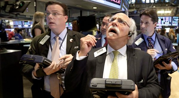 Peter Tuchman, foreground right, works with fellow traders on the floor of the New York Stock Exchange, Monday, Aug. 24, 2015. U.S. stock markets plunged in early trading Monday following a big drop in Chinese stocks.  (AP PHOTO/RICHARD DREW)