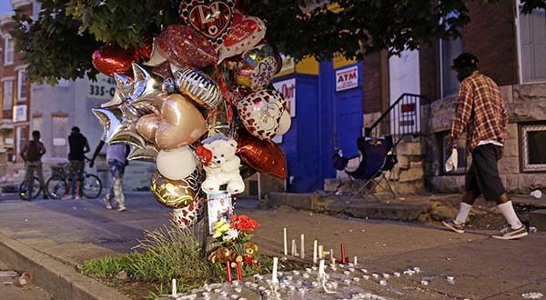 In this July 30, 2015 picture, balloons and candles mark a spot where a man was shot earlier in the week, in Baltimore. Murders are spiking again in Baltimore, three months after Freddie Gray's death in police custody sparked riots. This year's monthly bloodshed has twice reached levels unseen in a quarter-century. In May, Baltimore set a 25-year high of 42 recorded killings. After a brief dip in June, the homicide is soaring again. (AP Photo/Patrick Semansky)
