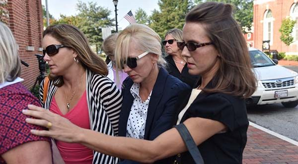 Molly Shattuck, second from right foreground, arrives at the Sussex County Courthouse in Georgetown, Del., for sentencing on Friday. Former Baltimore Ravens cheerleader Molly Shattuck has been sentenced to two years of probation after pleading guilty to raping a 15-year-old boy at a vacation rental home in Delaware. The 48-year-old collapsed to her knees after she was sentenced Friday morning and wept as she apologized.  (Kim Hairston/The Baltimore Sun via AP)