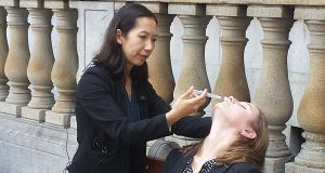 Dr. Leana Wen, Baltimore City Health Commissioner, demonstrates administering a dose of the opioid overdose antidote naloxone on her assistant, Katherine Warren, in August 2015.  (The Daily Record / Heather Cobun)