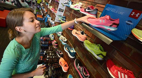 Kate Sachs reaches for  a pair of Under Armour Speedform Apollo running shoes  at Charm City Run in Locust Point in 2014. Under Armour wants to sell more products to women.(The Daily Record/Maximilian Franz)