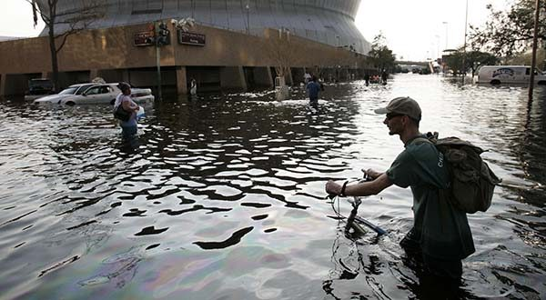 This Aug, 31, 2005 file photo shows a man pushing his bicycle through flood waters near the Superdome in  New Orleans after Hurricane Katrina left much of the city under water. A new but controversial study asks if an end is coming to the busy Atlantic hurricane seasons of recent decades. The Atlantic looks like it is entering in to a new quieter cycle of storm activity, like in the 1970s and 1980s, two prominent hurricane researchers wrote Monday in the journal Nature Geoscience.(AP Photo/Eric Gay, File)