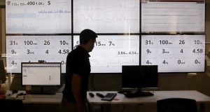 An employee in the software development department of DraftKings walks past screens displaying the company's online system stats in Boston in September. The legal landscape for daily fantasy sports is quickly getting complicated, with both states and members of Congress looking at ways to increase regulatory oversight. (Stephan Savoia/AP Photo)