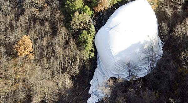 Members of the Army walk near part of an unmanned Army surveillance blimp in a wooded area near Muncy, Pa., Thursday, Oct. 29, 2015. The slow-moving, unmanned Army surveillance blimp broke loose from its mooring at Aberdeen Proving Ground in Maryland and floated over Pennsylvania for hours Wednesday afternoon causing electrical outages as its tether hit power lines. (Jimmy May/Bloomsburg Press Enterprise via AP)