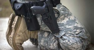 A member of the 139th Military Police Company kneels with his holstered 9mm Beretta M9 during a qualifying exercise at a small arms range on Sept. 29 in Fort Stewart, Ga. The Army wants to replace its M9, a 9mm semi-automatic handgun adopted during the Cold War. The new gun also will replace the smaller M11.  (AP Photo/Stephen B. Morton)