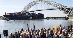 In this Sept. 21, 2010, file photo, the President Truman, a large cargo ship, passes under the Bayonne Bridge in Bayonne, N.J., as a group, including New Jersey Gov. Chris Christie and Lt. Gov. Kim Guadagno, listen to U.S. Rep. Albio Sires, D-N.J., talk about plans of a $1.3 billion project to raise the height of the bridge to give the larger, next generation of cargo ships access to New York and New Jersey ports.  Delays on a project to raise the Bayonne Bridge could lead to other East Coast ports losing out on larger cargo vessels that are expected to begin passing through an expanded Panama Canal next spring.   (AP Photo/Mel Evans, File)