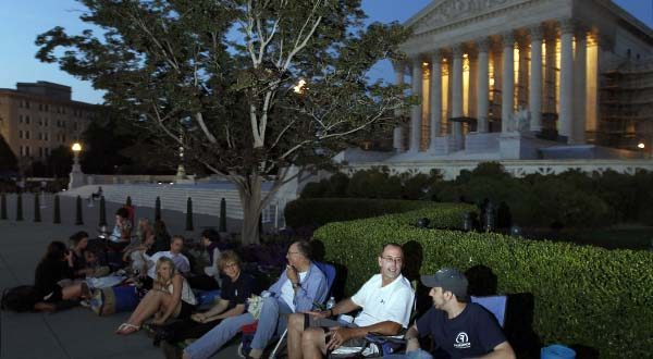 """In this June 27, 2012, file photo people line up in front of the U.S. Supreme Court on the eve of the expected ruling on whether or not the Affordable Care Act passes the test of constitutionality in Washington. The Supreme Court on Oct. 5, 2015, put a change in place that prohibits lawyers who are members of the Supreme Court bar from hiring """"line standers"""" to hold their place for seats to big arguments. The practice is common for congressional hearings, and has become more so in recent years for high-profile high court cases, including those involving gay marriage and the Obama health care overhaul. Lawyers who are part of the Supreme Court bar have access to a reserved section toward the front of the courtroom, and their odds of getting in are better than those for the general public. But now they will have to wait in line themselves if they want seats in the special section. (AP Photo/Alex Brandon, File)"""