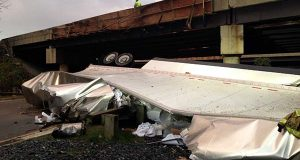In this photo provided by the Prince George's County Fire Department, the wreckage of a tractor trailer lies under an overpass in Suitland on Friday. Authorities say a driver was killed when the tractor trailer he was driving fell from a Capital Beltway overpass onto the Suitland Parkway.(Assistant Fire Chief Alan C. Doubleday/Prince George's County, Md. Fire Department via AP)