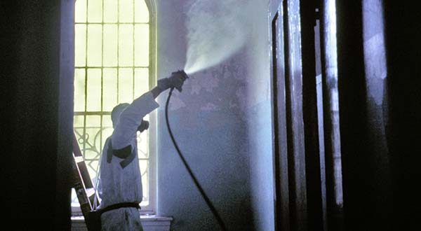 A worker wearing a protective mask and suit prepares a painted surface for wet scraping by first saturating it with water. Wet methods offered the best control of airborne lead levels, according to the U.S. Centers for Disease Control and Prevention. (U.S. Centers for Disease Control and Prevention photo)