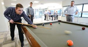 From Left, Ellin & Tucker employees David Konapelsky, Analyst; Zach Reichenbach, Manger; and David Frankenberger, Marketing Coordinator; enjoy a game of pool in the company dining and entertainment area on Friday evening after work. (The Daily Record/Maxmilian Franz)