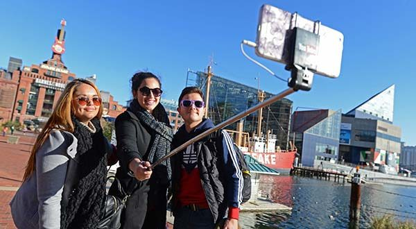 University of Texas El Paso students, Katie Salinas, left, Estefania Vazquez and Carlos Munoz take a group selfie at the Baltimore Inner Harbor while sightseeing after a weekend conference with the Society of Hispanic Professional Engineers in 2015.   (The Daily Record/Maximilian Franz)