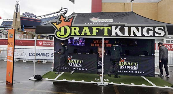 In this Oct. 25  photo, workers set up a DraftKings promotions tent in the parking lot of Gillette Stadium, in Foxborough, Mass., before an NFL football game between the New England Patriots and New York Jets. (AP Photo/Charles Krupa, File)