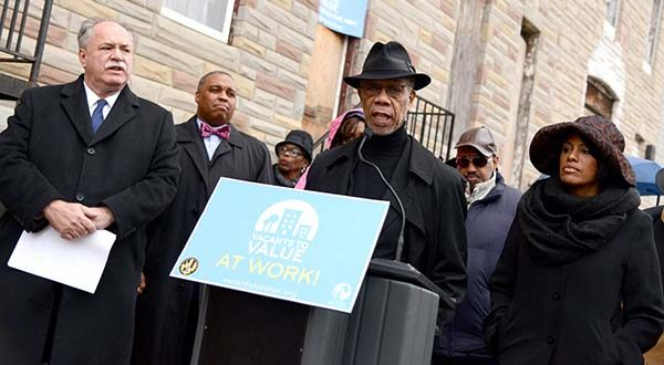 Pastor H. Walden Wilson, center, of Israel Baptist Church, speaks about how the neighbors of the vacant row homes on the 2000 block of East Biddle street have been waiting for years to have the houses taken down. (The Daily Record/Maximilian Franz)