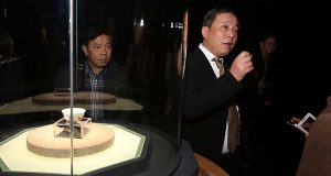 """In this Dec. 18, 2014 photo, Chinese billionaire and art collector Liu Yiqian, right, speaks at an opening ceremony in Shanghai, China, for the exhibition of a $36 million Ming Dynasty tea cup, at left, he bought and paid for with his American Express card. Liu was the winning bidder for Amedeo Modigliani's """"Reclining Nude"""" at a Christie's auction earlier this month - offering $170.4 million - and when the sale closes he'll be putting it on his American Express card. (Chinatopix via AP)"""