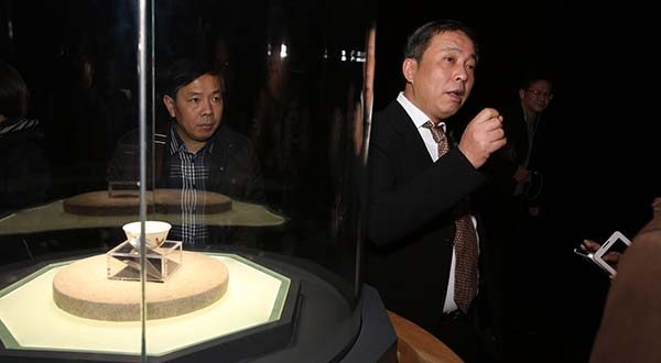 "In this Dec. 18, 2014 photo, Chinese billionaire and art collector Liu Yiqian, right, speaks at an opening ceremony in Shanghai, China, for the exhibition of a $36 million Ming Dynasty tea cup, at left, he bought and paid for with his American Express card. Liu was the winning bidder for Amedeo Modigliani's ""Reclining Nude"" at a Christie's auction earlier this month - offering $170.4 million - and when the sale closes he'll be putting it on his American Express card. (Chinatopix via AP)"