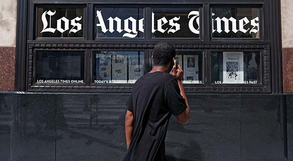 In this Oct. 5 file photo, a pedestrian walks past the Los Angeles Times building in downtown Los Angeles. Tribune Publishing, the owner of the Baltimore Sun, Los Angeles Times, Chicago Tribune and other newspapers, said Thursday, Nov. 12, 2015, it expects a buyout offer to cut its staff by 7 percent. Chicago-based Tribune Publishing Co. owns 11 major daily newspapers. (AP Photo/Richard Vogel, File)