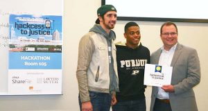 Cody Meshberger, left, and Chris Price receive their second-place award from judge Bill O'Boyle of Citrix during the Hackcess to Justice event last month in Raleigh, N.C. The duo created what they describe a as a 'total legal help site.' (David Donovan)