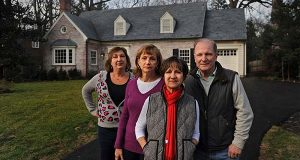 In this Dec. 13, 2015 photo, neighbors Diane Rosenburg, from left, Sheila Leiber and Laura and Brad Creer pose for a photo in front of a home they bought to keep it from being torn down, in Bethesda, Md. Neighbors pooled $2 million to buy, modernize and resell the old home. The trio hope the updated brick Colonial, will preserve the charm of their neighborhood and maybe even make them a modest profit. (Michael S. Williamson/The Washington Post via AP)