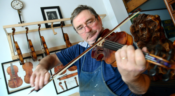 Igor Gersh, the luthier at Ted's Musician Shop in Baltimore, tests a violin he recently repaired in his workshop. The trained viola player has been repairing stringed instruments for more than 20 years and gets regular visits from students at the neighboring Peabody Institute. (Maximilian Franz/The Daily Record)